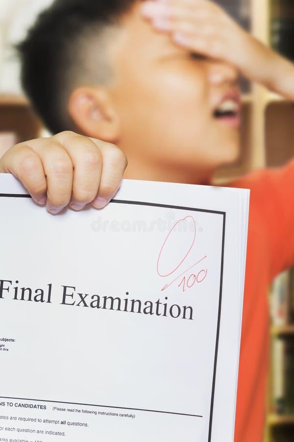 Garçon asiatique avec le score zéro sur le papier d'examen image stock