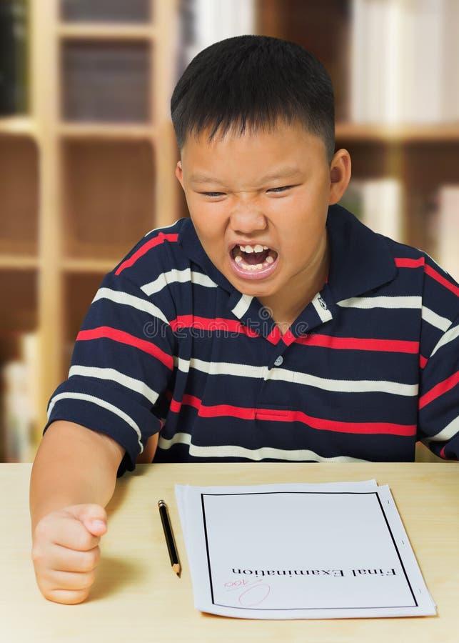 Garçon asiatique contrarié avec son résultat d'examen photo libre de droits