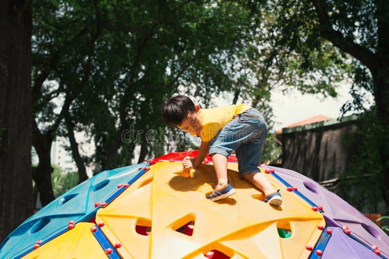 Garçon asiatique d'enfant ayant l'amusement à jouer sur le jouet s'élevant des enfants au terrain de jeu d'école, de nouveau à l' photographie stock
