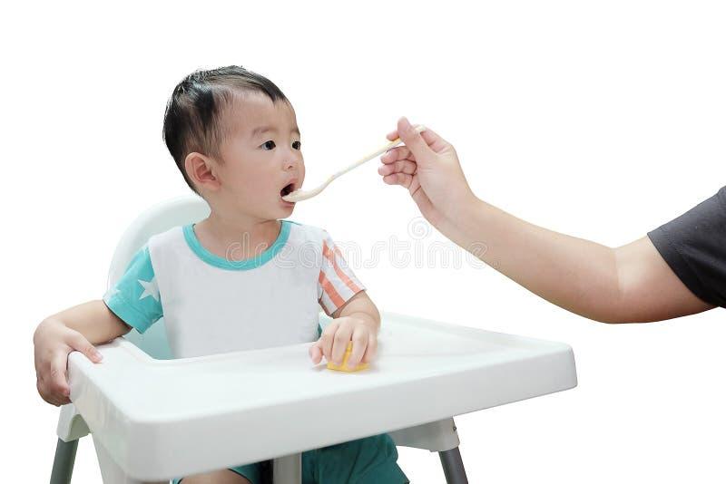 Garçon asiatique d'enfant mangeant avec la cuillère, d'isolement sur le fond blanc photos stock