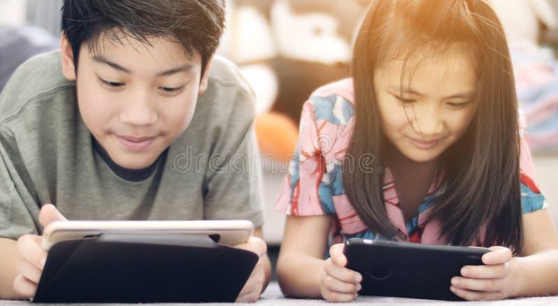 Garçon asiatique et fille jouant le jeu au téléphone portable ainsi que le visage de sourire images libres de droits