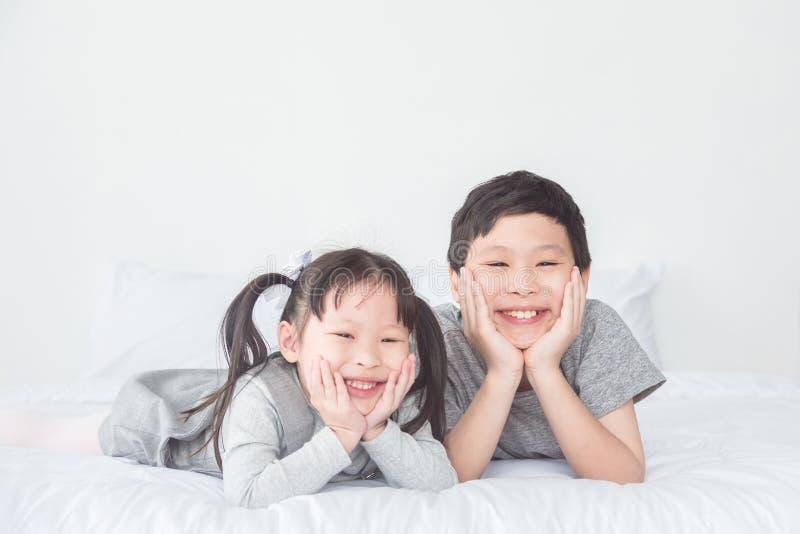 Garçon asiatique et fille se trouvant sur le lit et le sourire à l'appareil-photo photo libre de droits