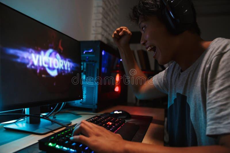 Garçon asiatique heureux de gamer gagnant tout en jouant des jeux vidéo sur le compu photographie stock libre de droits