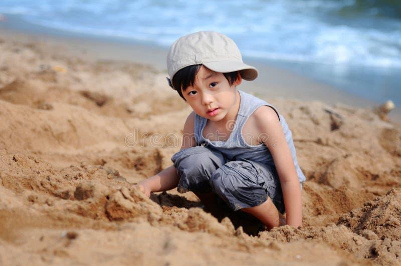 Garçon asiatique jouant sur la plage photographie stock