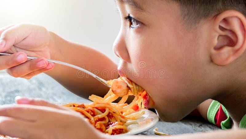Garçon asiatique mangeant des spaghetti photographie stock libre de droits