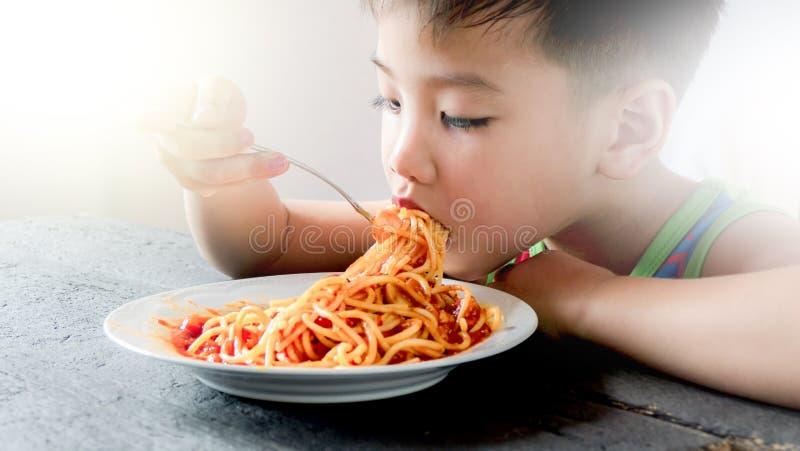 Garçon asiatique mangeant des spaghetti images libres de droits