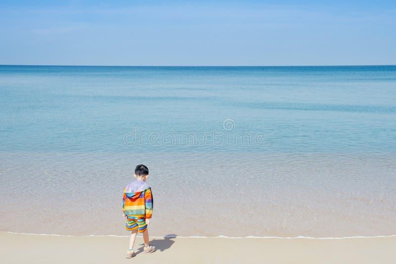 Garçon asiatique marchant sur la mer d'extérieur de plage et le ciel bleu photo stock