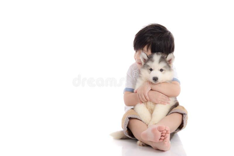 Garçon asiatique mignon s'asseyant avec le chiot de chien de traîneau sibérien image libre de droits