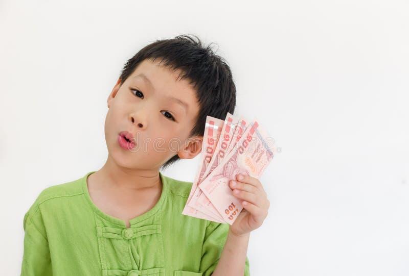 Garçon asiatique pensant avec tenir l'argent thaïlandais en main photos stock