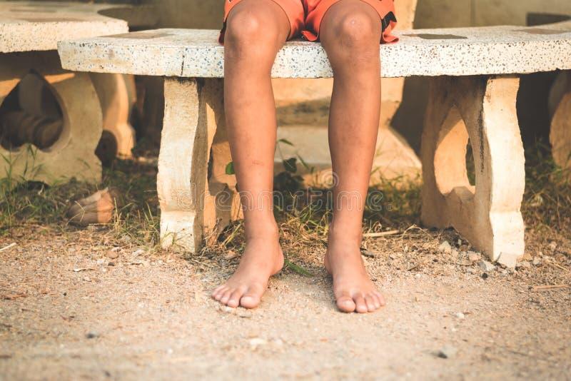 Garçon asiatique s'asseyant au-dessus du banc de marbre image stock