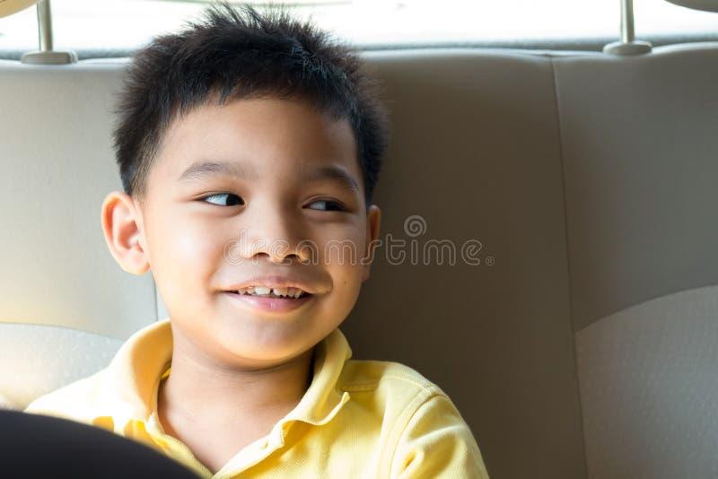 Garçon asiatique souriant sur le siège arrière image stock