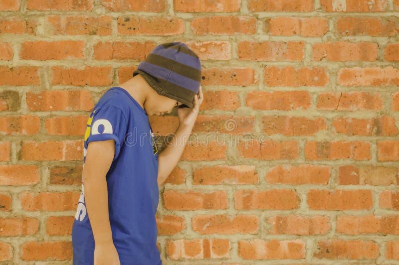 Garçon asiatique vêtements de rue de port d'usage de chapeau, effort et pression, mur de briques orange de fond avec l'espace de  photos stock