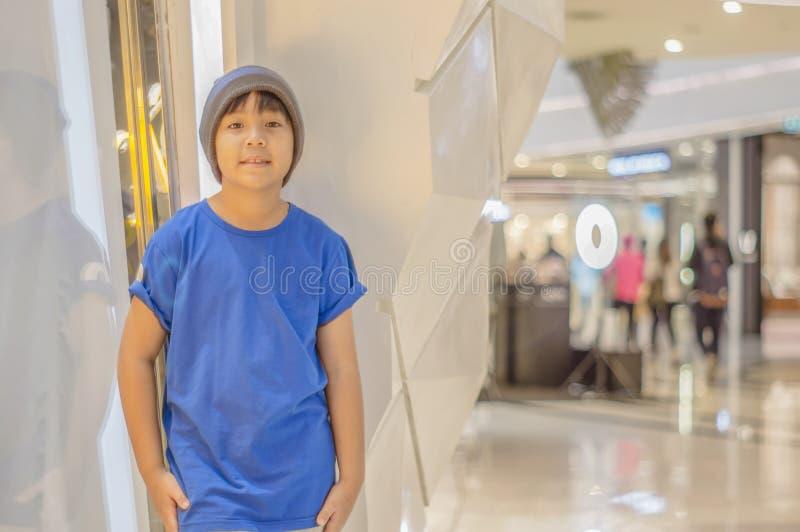 Garçon asiatique vêtements de rue de port d'usage de chapeau, sourire souriant heureusement dans le mail images libres de droits