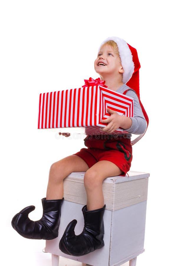Garçon assez petit avec le costume d'aide de Santa Claus tenant le grand boîte-cadeau rayé et recherchant photographie stock