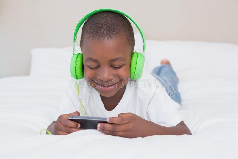 Download Garçon Assez Petit Employant Le Smartphone Et La Musique De écoute Dans Le Lit Photo stock - Image du maison, ménage: 56483822