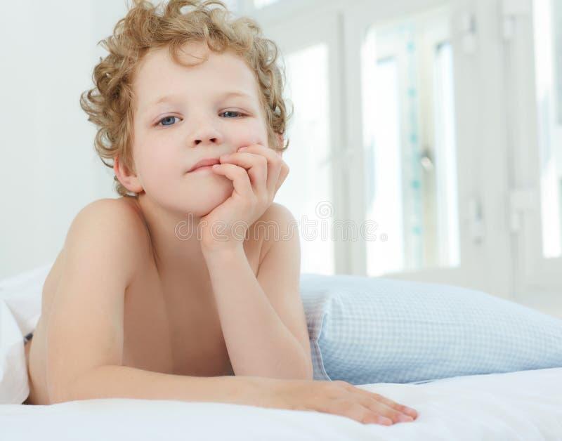 Garçon aux cheveux bouclés fatigué se situant dans le lit étayé vers le haut des mains une tête Il temps du `s de se lever image libre de droits