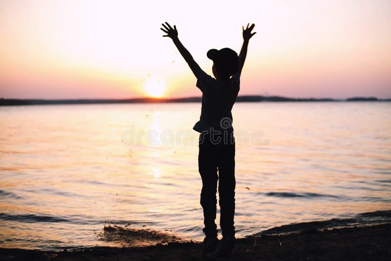 Garçon aux stands de coucher du soleil dessus sur la plage p photos libres de droits
