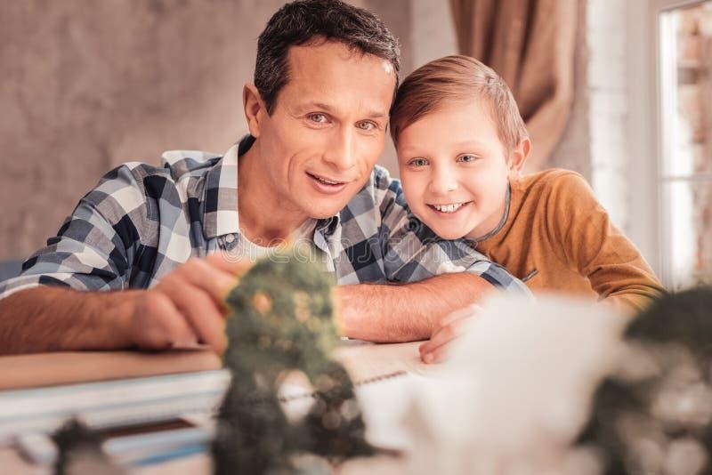 Garçon aux yeux bleus de sourire se penchant sur son épaule de père photo libre de droits
