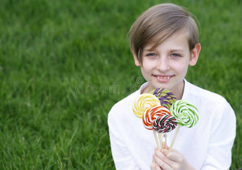 Garçon avec des bonbons sur une sucette photographie stock