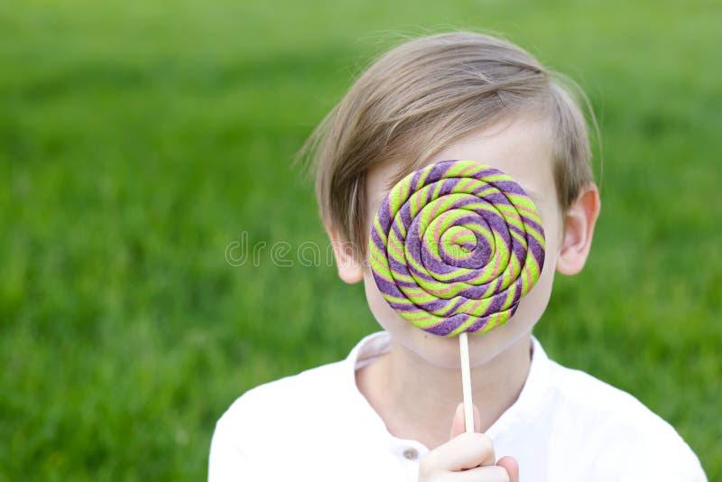 Garçon avec des bonbons sur une sucette image stock