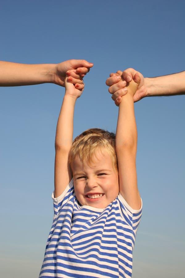 Garçon avec des mains de parents image libre de droits