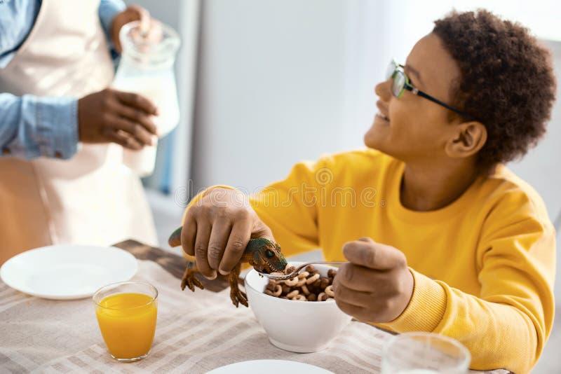 Garçon avec du charme causant avec le père tout en jouant pendant le petit déjeuner photos libres de droits