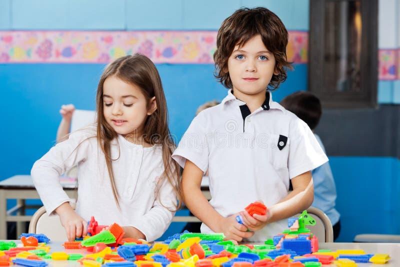 Garçon avec l'ami féminin jouant des blocs dans la salle de classe photo libre de droits