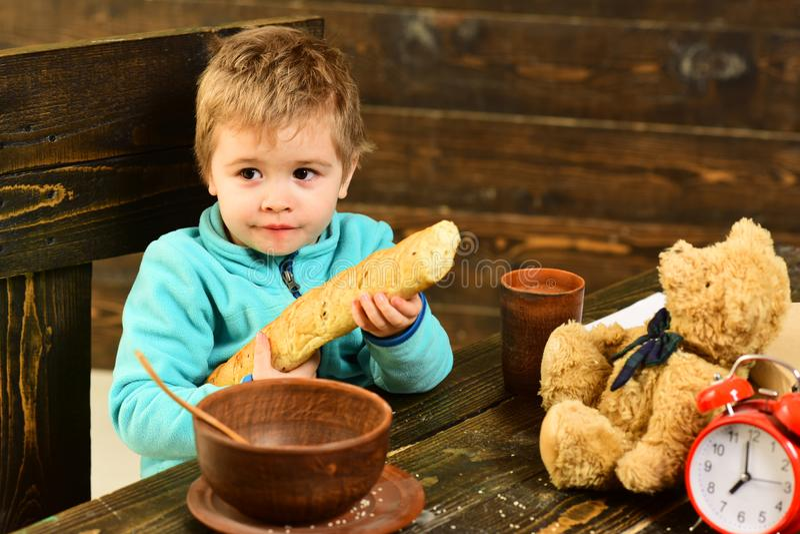 Garçon avec l'ours français de baguette et de nounours à la table Le garçon apprécient le dîner avec l'ami de jouet Petit garçon  image libre de droits