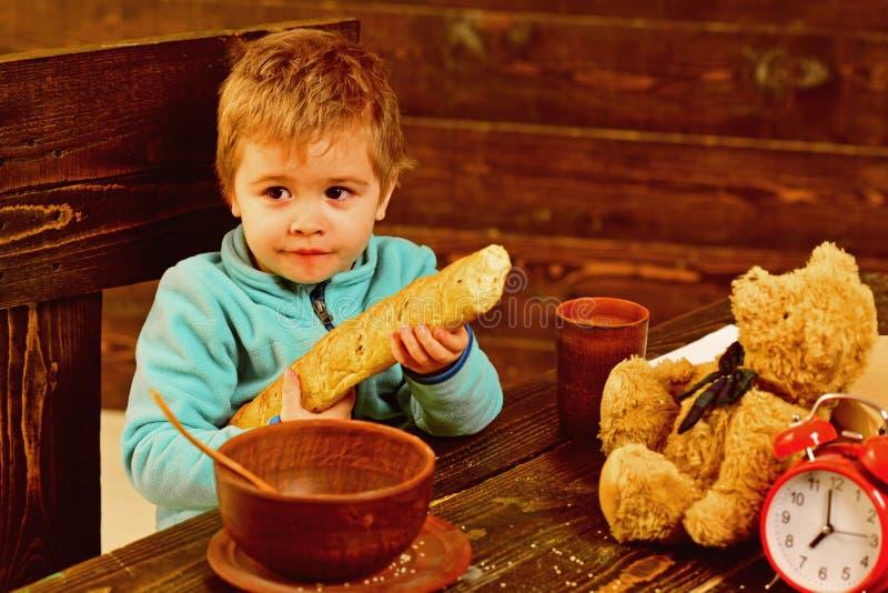 Garçon avec l'ours français de baguette et de nounours à la table Le garçon apprécient le dîner avec l'ami de jouet Petit garçon  photos libres de droits