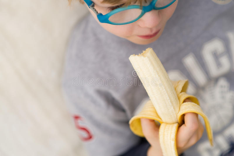 Garçon avec la banane - enfant mangeant la banane image libre de droits