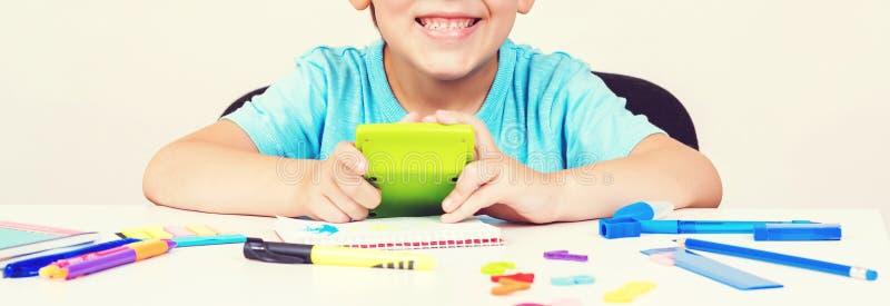 Garçon avec la calculatrice faisant le travail à la maison L'enfant s'assied à un bureau à l'intérieur De nouveau à l'école Les g images stock