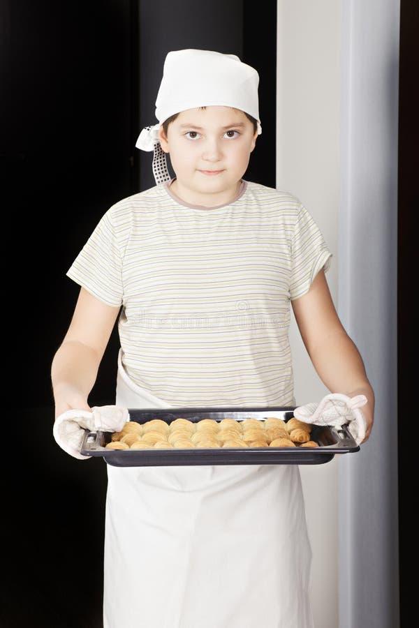 Garçon avec la casserole de croissants image stock