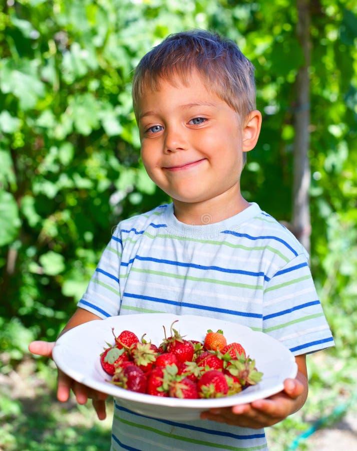 Garçon avec la fraise. photographie stock libre de droits