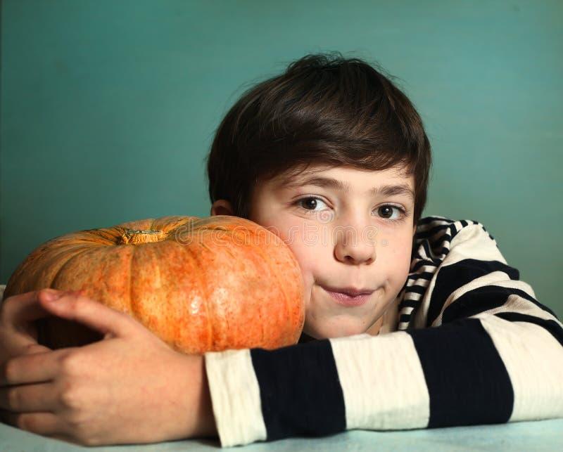 Garçon avec la grande fin orange de potiron vers le haut du portrait photos stock