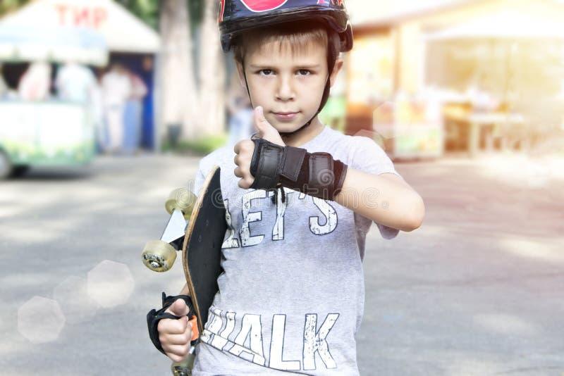 Garçon avec la planche à roulettes montrant des pouces  photos libres de droits