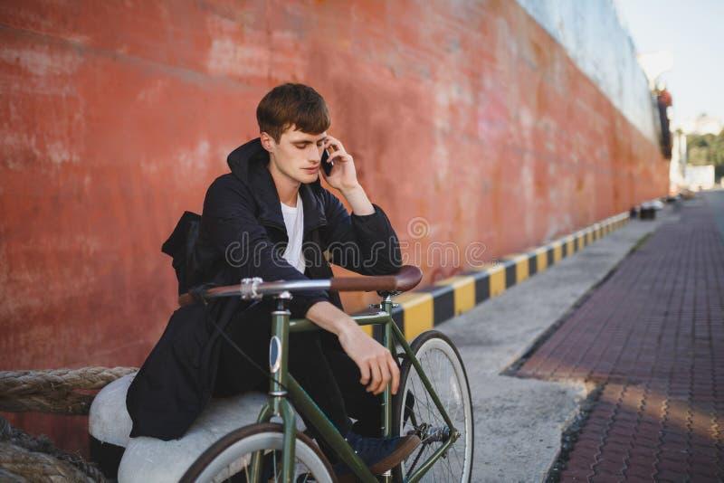 Garçon avec la séance brune de cheveux tout en se penchant sur la bicyclette et parlant sur son téléphone portable Jeune homme da photo libre de droits