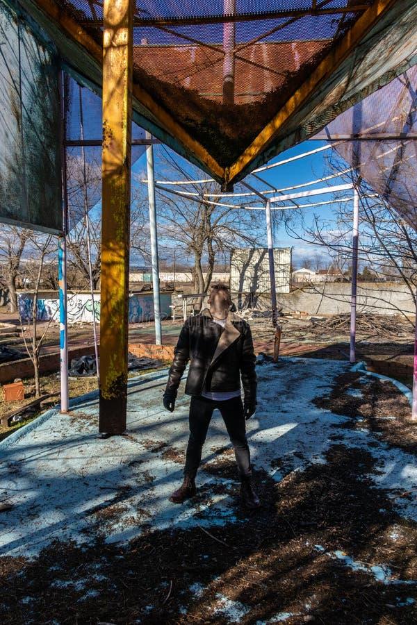 Garçon avec la veste en cuir posant dans un vieil endroit abandonné images libres de droits