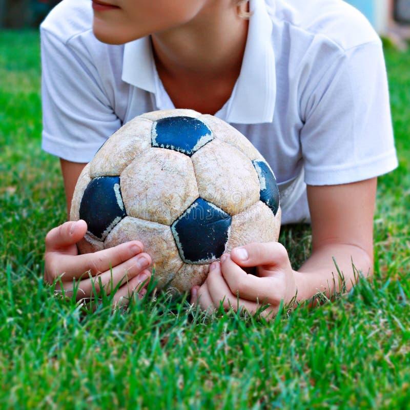 Garçon avec la vieille bille de football photos stock