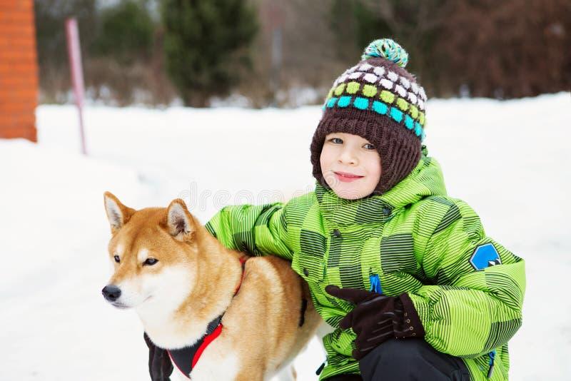 Garçon avec le chien de Shiba Inu dehors pendant l'hiver photos stock