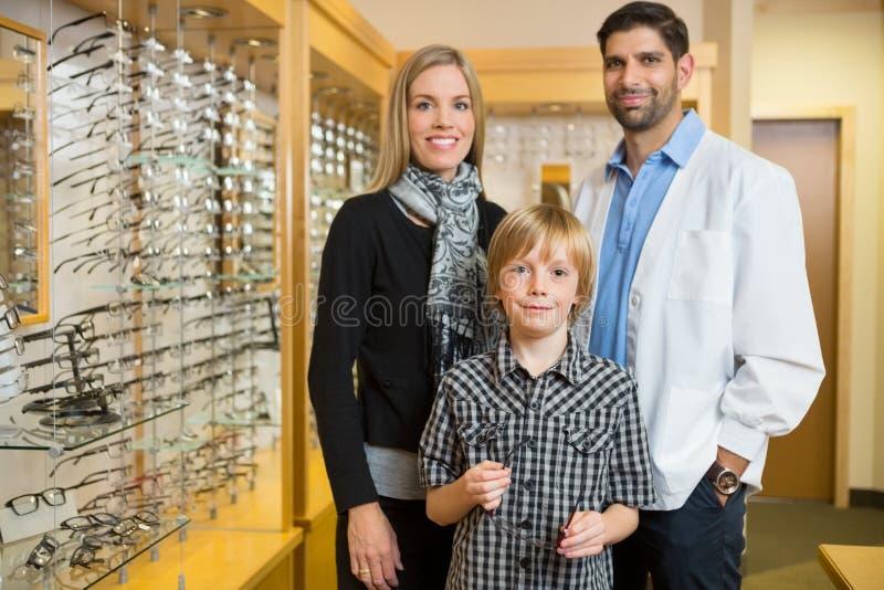 Garçon avec le magasin d'And Mother In d'optométriste photos stock