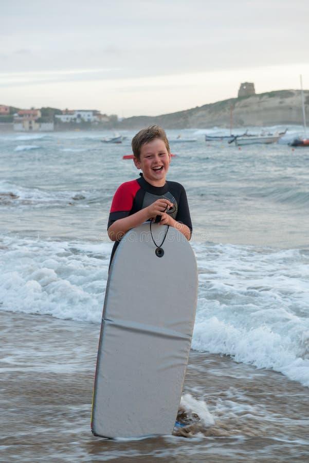 Garçon avec le panneau de ressac au bord de mer image libre de droits