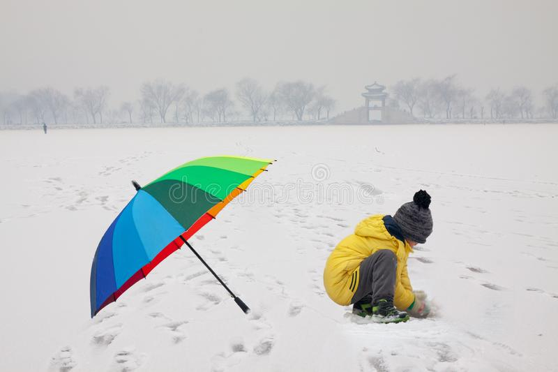 Garçon avec le parapluie dans le palais d'été neigeux photographie stock libre de droits