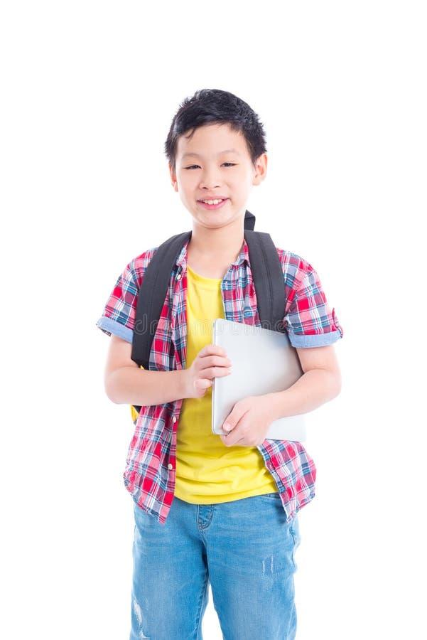 Garçon avec le sac à dos tenant l'ordinateur portable et les sourires photographie stock