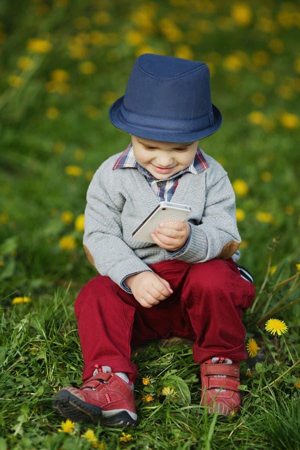 Download Garçon Avec Le Téléphone Se Reposant Sur L'herbe Image stock - Image du garçon, famille: 45350695