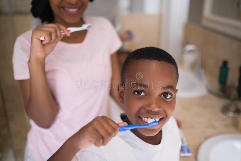 Garçon avec les dents de brossage de mère à la maison photo stock