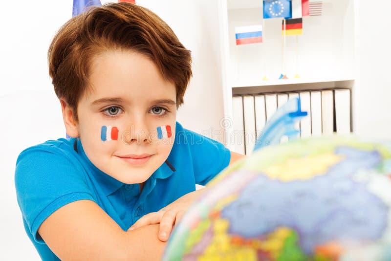 Garçon avec les drapeaux français sur ses joues à la salle de classe images libres de droits