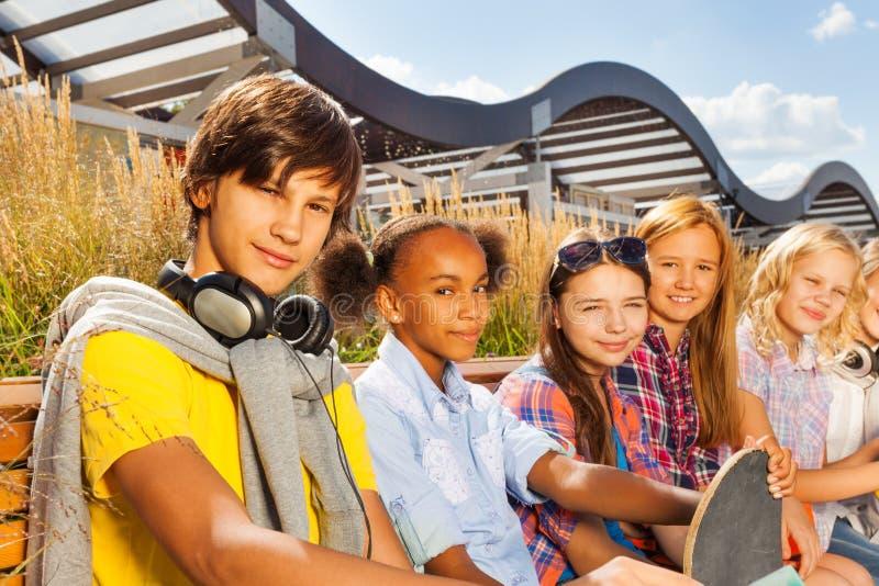 Garçon avec les filles de sourire sur le banc tenant la planche à roulettes image libre de droits