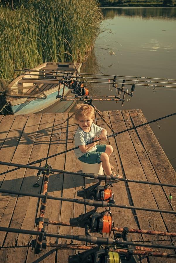 Garçon avec les poissons contagieux de canne à pêche pendant l'été image stock