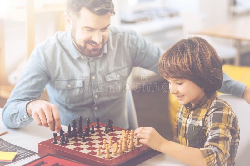 Garçon avec plaisir positif faisant le premier mouvement d'échecs photographie stock libre de droits