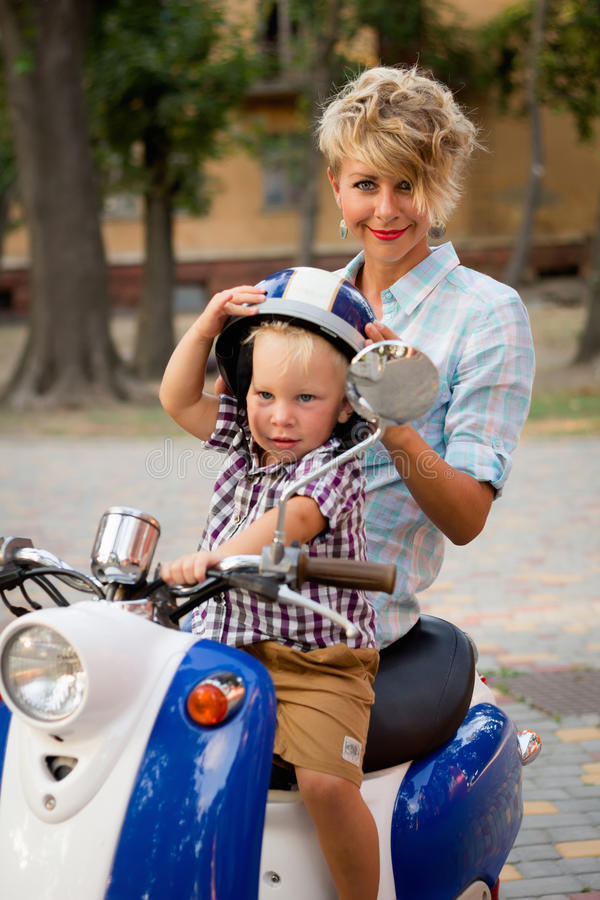 Garçon avec sa mère s'asseyant sur le scooter photo libre de droits
